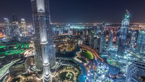 Paniramic skyline view of Dubai downtown with mall, fountains and Burj Khalifa aerial night timelapse