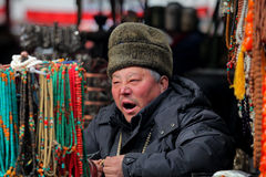 Panjiayuan market Beijing. Beijing, China - January 19, 2013: Man selling on biggest and best-known antiques market, Panjiayuan in Beijing, China Stock Photos