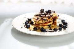 Pankcakes con los ar?ndanos y el jarabe de arce Desayuno dulce foto de archivo
