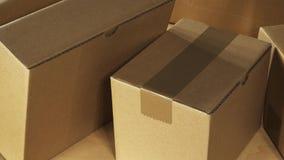 Panna över bruna lådaaskjordlotter som staplas på träkontorsskrivbordet som är klart för sändning eller levereras precis stock video