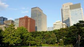 Panna av kontorsbyggnader som omges av träd i centrala Tokyo Japan lager videofilmer