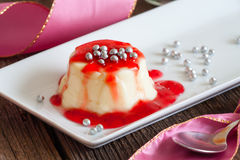 Panna cotta. Italian dessert made by simmering together cream, milk and sugar, mixing this with gelatin, and letting it cool until set. Here with raspberry Royalty Free Stock Image
