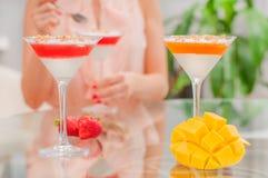Panna cotta dessert with fruit jelly. Woman eating dessert. Stock Photography