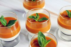 Panna cotta dessert with mango puree with mint leaves in a glass on a marble table stock photo