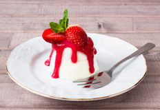 Panna cotta dessert with strawberry sirup and mint leaf. On light wooden background Royalty Free Stock Image
