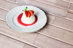 Panna cotta dessert with strawberry sirup and mint leaf. On light wooden background. space for text Stock Image
