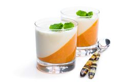 Panna cotta with orange jelly in clear glass isolated on white. Panna  cotta with orange jelly in clear glass isolated on white royalty free stock photography