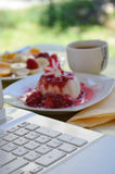 Panna Cotta with raspberry sauce. Picture of a Panna Cotta with raspberry sauce.Morning with sweet fresh panna cotta, cup of coffee an laptop Stock Photo