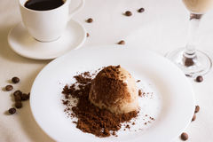 Panna cotta topped with grated chocolate on a white plate Royalty Free Stock Image