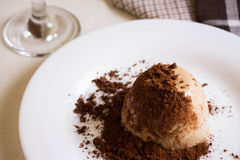Panna cotta topped with grated chocolate on a white plate Royalty Free Stock Photos