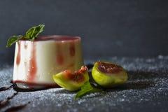 Panna-Cottanachtisch mit frischen Feigenfrüchten auf dunklem Hintergrund stockfotos