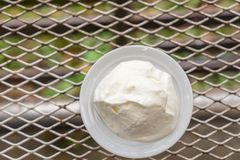 Panna da montare nella tazza bianca sulla tavola del metallo Immagine Stock Libera da Diritti