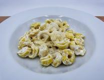 Panna di alla dei tortellini con parmigiano in un piatto bianco, pasta italiana immagini stock libere da diritti