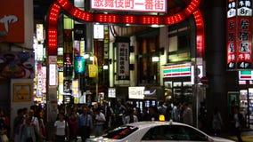 Panna för Tid schackningsperiod av det upptagna Shinjuku underhållning-/shoppingområdet på natten - Tokyo Japan lager videofilmer