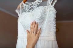 Panna młoda adoruje ślubną suknię, biel koronkę, panny młodej rękę z koronką i manicure, ranek panna młoda obrazy stock