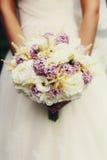 Panna młoda chwyty w jej rękach bukiet białe róże i fiołkowy lil Zdjęcia Stock