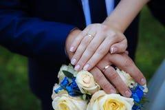 Panna młoda x27 i groom&; s ręki z obrączkami ślubnymi na bukiecie kwiaty obrazy royalty free