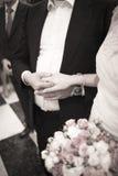 Panna młoda i nowożeniec w ślubnych małżeństwo ceremonii mienia rękach Zdjęcie Stock