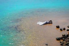 Panna młoda lub kobieta w ślubnej sukni kłaść na morze plaży Obrazy Royalty Free
