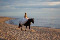 Panna młoda na koniu przy zmierzchem morzem Zdjęcie Stock