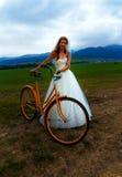 Panna młoda na pomarańczowym rowerze w pięknej ślubnej sukni z koronką w krajobrazie Zdjęcia Stock