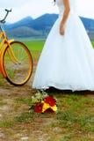 Panna młoda na pomarańczowym rowerze w pięknej ślubnej sukni z koronką w krajobrazie z ślubnym bukietem pojęcia sukni panny młode Obraz Royalty Free