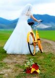 Panna młoda na pomarańczowym rowerze w pięknej ślubnej sukni z koronką w krajobrazie z ślubnym bukietem pojęcia sukni panny młode Zdjęcia Stock