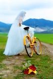Panna młoda na pomarańczowym rowerze w pięknej ślubnej sukni z koronką w krajobrazie z ślubnym bukietem pojęcia sukni panny młode Zdjęcie Stock