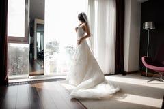 Panna młoda patrzeje przez okno w białej koronkowej ślubnej sukni i przesłona obrazy royalty free