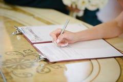 Panna młoda podpisuje na rejestracji w dokumencie na dzień ślubu zdjęcia royalty free