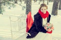 Panna młoda przy ślubem w zimie w białej sukni i czerwonym szaliku w czerwonych mitynkach Zdjęcie Royalty Free