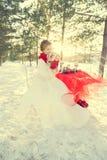 Panna młoda przy ślubem w zimie w białej sukni i czerwonym szaliku w czerwonych mitynkach Obraz Stock
