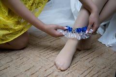 Panna młoda stawia na ślubnej podwiązce obraz royalty free
