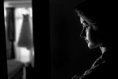 Panna młoda stoi zamyślenie w ciemnym pokoju Fotografia Royalty Free