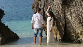 panna młoda stojaki w wodzie przeciw skale, fornalów uściśnięcia i komes i zdjęcie wideo