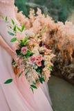 Panna młoda trzyma nieociosany ślubny bukieta składać się z różni kwiaty Dekoraci grafika Obraz Stock