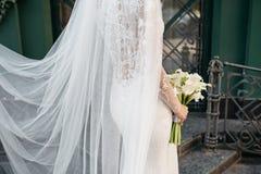 Panna młoda trzyma pięknego białego ślub kwitnie bukiet Zdjęcie Stock