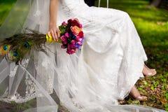 Panna młoda ubierał w biel koronki przesłonie z bukietem i sukni kwiaty i pawi piórka Zdjęcie Royalty Free