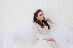 Panna młoda w ślubnej sukni obsiadaniu na leżance Obrazy Stock