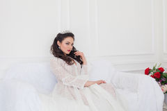Panna młoda w ślubnej sukni obsiadaniu na leżance Obrazy Royalty Free