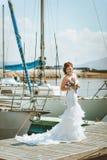 Panna młoda w białej ślubnej sukni z pociągiem, stojaki na molu przesyła Obrazy Royalty Free