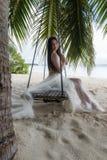Panna młoda w białej sukni jedzie na huśtawce pod dużym drzewkiem palmowym obraz stock