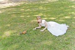 Panna młoda w białym lying on the beach na trawie obok wiewiórki Fotografia Stock