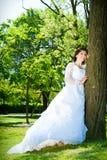 Panna młoda w biel Przy parkiem blisko drzewa zdjęcia royalty free