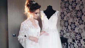 Panna młoda w boudoir ogląda jej ślubną suknię zbiory