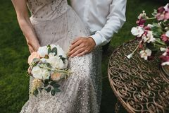 Panna młoda w pięknej beż sukni z beading siedzi na podołku z ślubnym bukietem w ręce Zdjęcia Stock