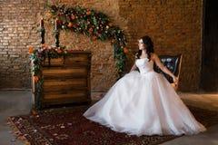 Panna młoda w pięknym ślubnej sukni obsiadaniu zdjęcie royalty free