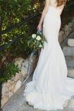Panna młoda w pięknym długim białym ślubnej sukni mienia bukiecie kwiaty Obraz Royalty Free