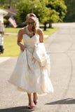 Panna młoda wycieczkuje up jej suknię i odprowadzenie puszek droga. Obrazy Stock