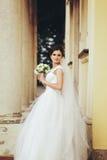 Panna młoda z ślubnym bukietem w jej ręk pozach w przejściu był Fotografia Royalty Free